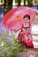 Girl with umbrella looking at flower