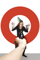 Hand aiming a pistol at a businesswoman with party hat