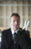 Hand holding pliers with gagged businessman looking at it