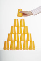 Hand placing disposable cup on top of stack