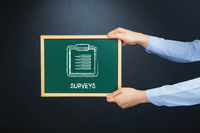 Popular : Hands holding blackboard with surveys concept