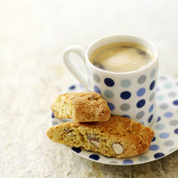 Italian espresso in spotty blue cup with cantuccini biscuits