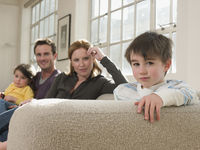 Little boy on sofa with family
