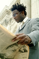 Low angle view of a man in business suit with sunglass reading newspaper