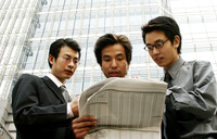 Low angle view of three businessmen sharing a newspaper