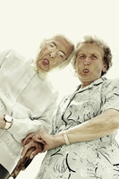 Low angle view of two old women showing their tongues at the camera
