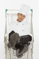 Male chef resting in a shopping cart