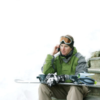 Male snowboarder talking on the phone