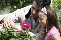 Man and girl planting flowers