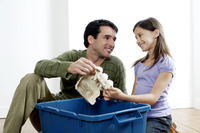 Man and girl putting empty egg carton into recycling container