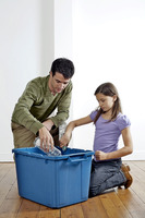 Man and girl putting plastic bottles into a recycling container