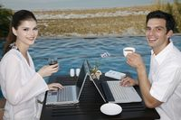 Man and woman drinking while using laptop