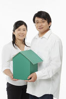 Man and woman holding a cardboard house