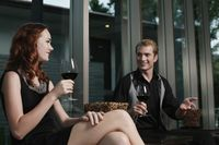 Man and woman holding glasses of red wine while chatting