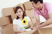 Man and woman packing potted plant into cardboard box