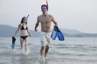 Man and woman running on beach with snorkeling gear