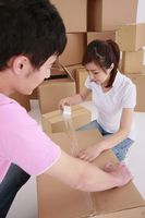 Man and woman taping up cardboard boxes