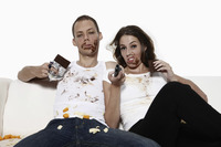 Man and woman watching television and eating chocolate on the couch