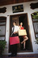 Man and woman with shopping bags standing at the doorway
