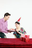Man bringing out a surprise birthday cake for woman