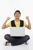 Man cheering while using laptop