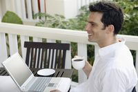 Man drinking coffee while using laptop