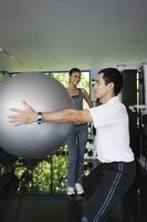 Man exercising with fitness ball, woman watching