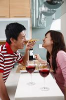 Man feeding woman pizza