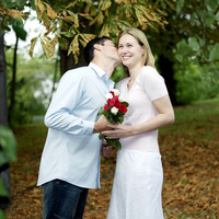Man giving his girlfriend a peck on the cheek after presenting her with flowers