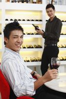 Man holding a glass of wine, another man is choosing wine