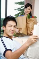 Man holding newspaper, woman in the background carrying groceries