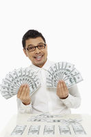 Man holding piles of cash