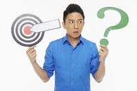 Man holding up a dart board along with a question mark symbol