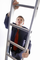 Man in business suit climbing up a ladder