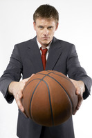 Man in business suit holding a basketball