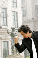 Man in business suit imitating a statue's pose