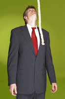 Man in business suit looking at a rope hanging from the top