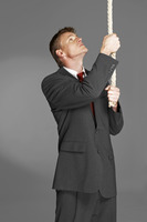 Man in business suit pulling a rope hanging from the top