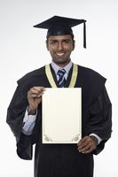 Man in graduation robe holding blank placard