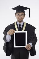 Man in graduation robe showing digital tablet