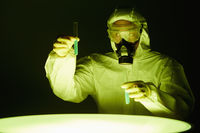 Man in protective suit holding test tubes