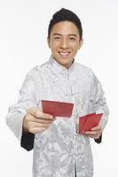 Man in traditional clothing handing out red packets