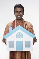 Man in traditional clothing holding a cutout house