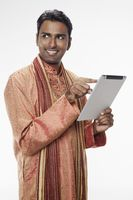 Man in traditional clothing using digital tablet
