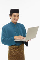 Man in traditional clothing using laptop