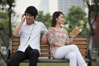 Man listening to music on the headphones, woman reading book on the bench