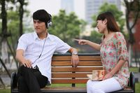 Man listening to music on the headphones, woman scolding man