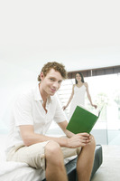 Man reading book with his girlfriend standing in the background
