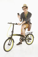 Man reading text message while sitting on the bicycle