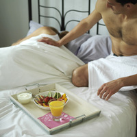 Man serving a tray of breakfast for is sleeping wife